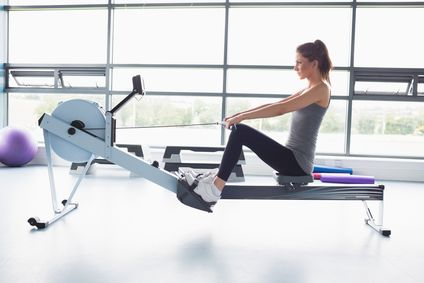 Woman working out on row machine in gym
